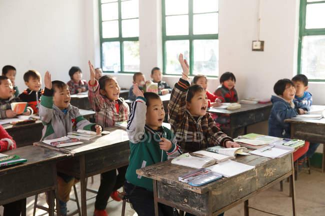 Des élèves chinois lèvent la main dans une école primaire rurale — Photo de stock