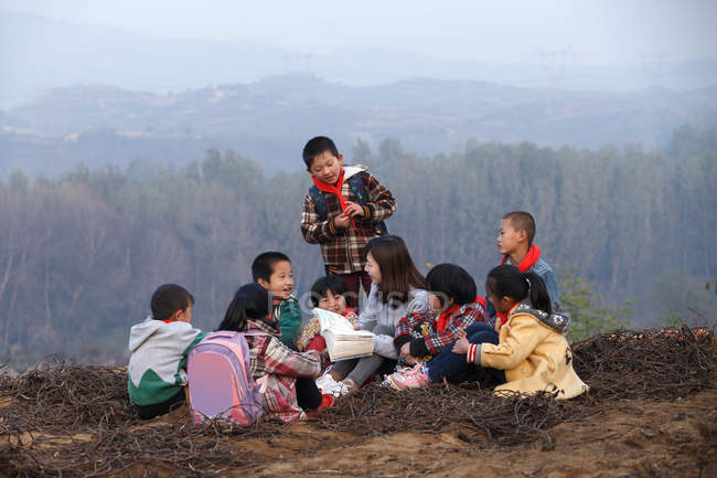 Happy rural teacher and pupils in outdoor learning — стокове фото