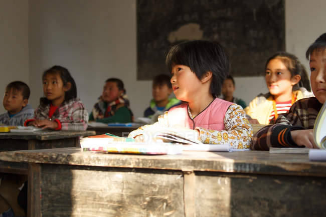 Chinese school students sitting at desks and studying in rural primary school — стокове фото