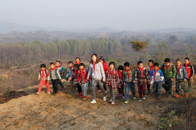 Young female teacher and rural chinese school students playing outdoor — стокове фото