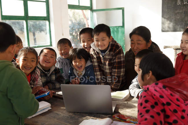 Rural female teacher and chinese pupils using laptop computer in classroom — стокове фото