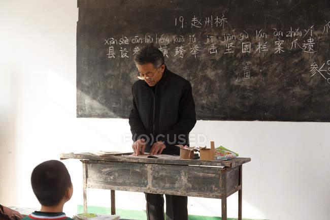Maschio cinese scuola elementare rurale insegnante in classe — Foto stock
