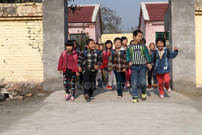 Heureux élèves ruraux chinois rentrant à la maison de l'école — Photo de stock