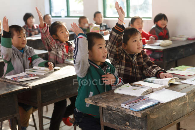 Chinese school students raising hands in rural primary school — Stock Photo