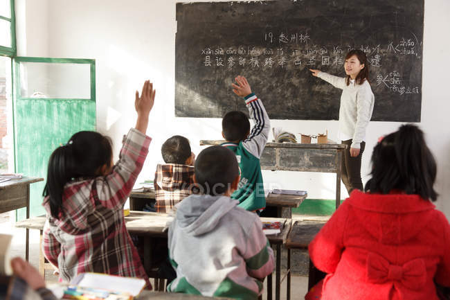 Rural female teacher pointing at chalkboard and chinese pupils raising hands in the classroom — Stock Photo