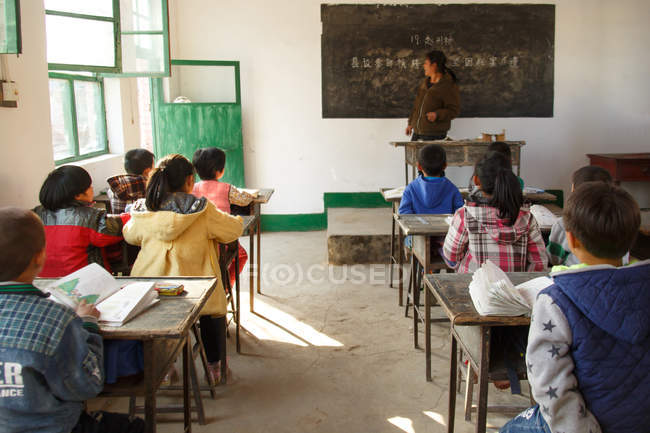 Rural female teacher standing near chalkboard and chinese pupils sitting at desks in the classroom — Stockfoto