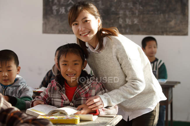 Happy chinese rural female teacher and pupils in classroom — стокове фото