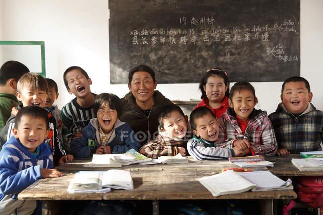 Сельская китайская учительница и ученики улыбаются перед камерой в классе — стоковое фото