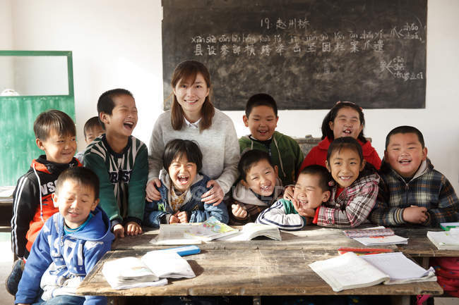Китайський сільський вчитель і учні посміхаються на камеру в класі — стокове фото