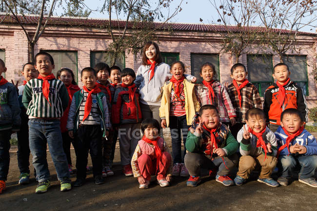 Rural female teacher and happy chinese pupils standing together in school yard — стокове фото