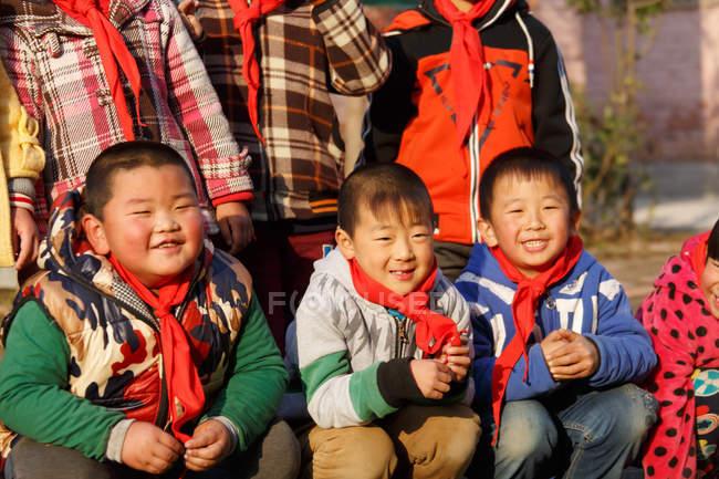 Счастливые сельские китайские ученики улыбаются перед камерой на открытом воздухе, обрезанный снимок — стоковое фото