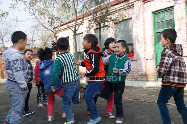 Chinese elementary school students playing games at school yard — Stock Photo