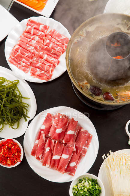 Close-up view of mutton hotpot with delicious ingredients on table, Chinese New Year concept — Stock Photo