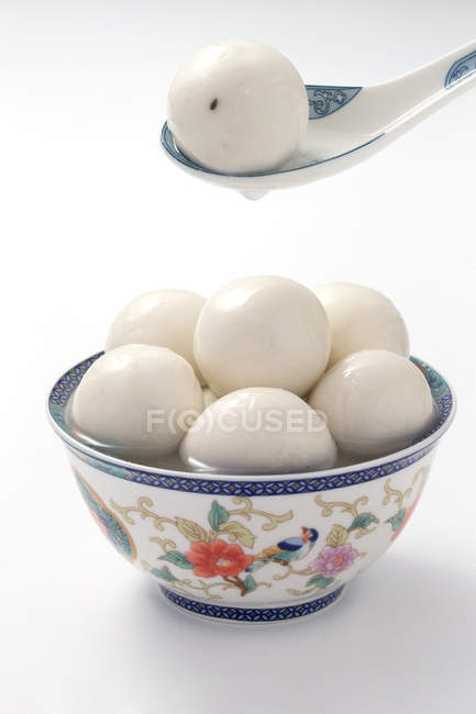 Close-up view of porcelain spoon and bowl with glutinous rice balls on white — Stockfoto