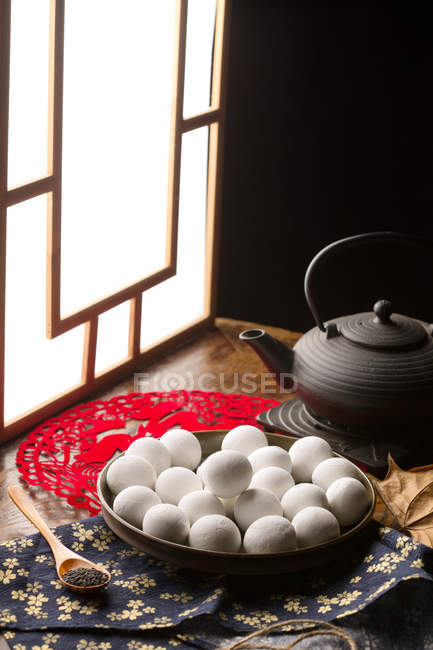 Glutinous rice balls on plate and black teapot on table — Stockfoto