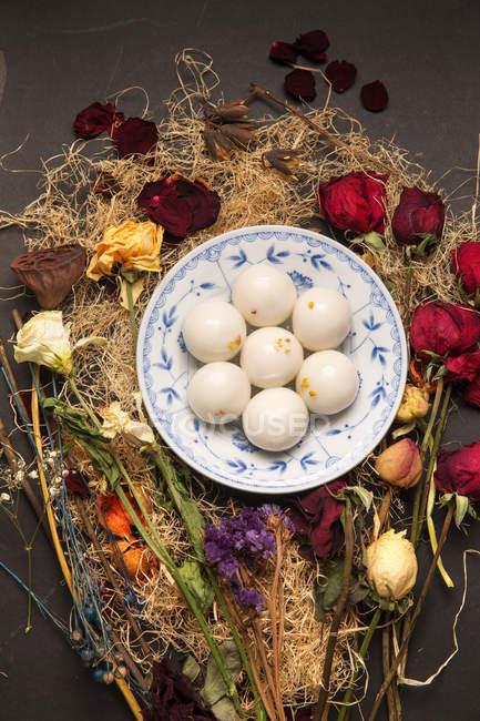 Draufsicht auf klebrige Reisbällchen für Laternenfest und getrocknete Blumen auf Holztisch — Stockfoto