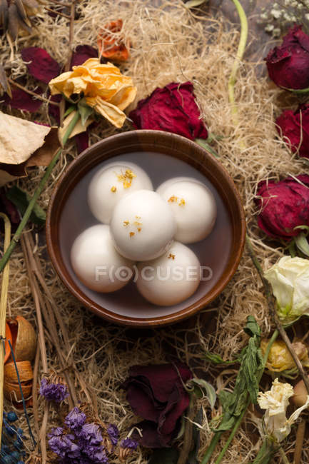 Top view of bowl with syrup and glutinous rice balls, dry flowers on table — Stockfoto