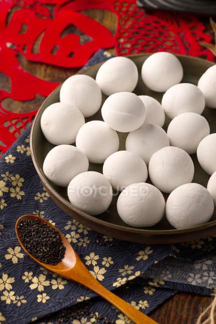 Nahaufnahme von klebrigen Reisbällchen auf Teller und Sesam in Holzlöffel auf Tisch — Stockfoto