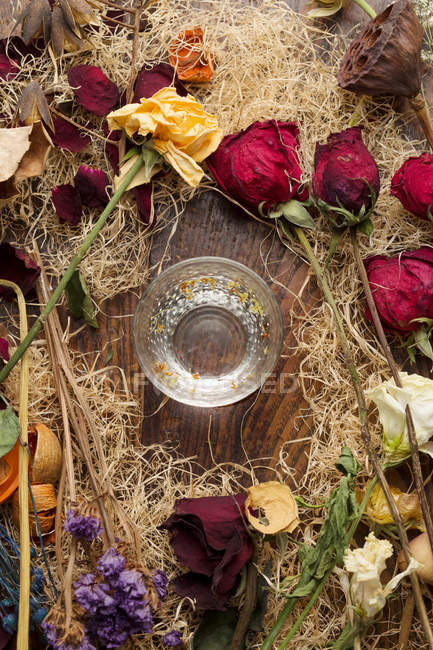 Vista superior de belas várias flores secas arranjadas e vidro na mesa de madeira — Fotografia de Stock