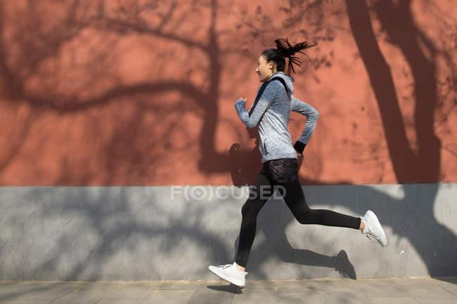 Vista lateral de joven asiática deportista corriendo en la calle - foto de stock