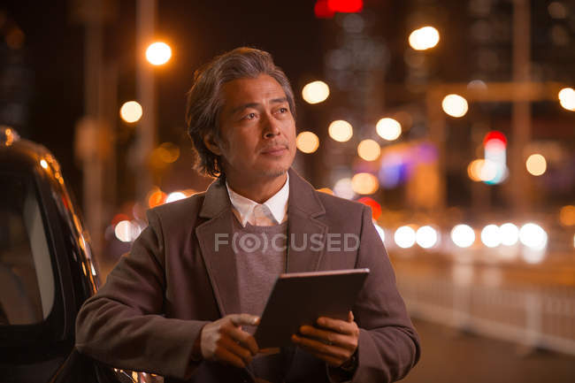 Mature asian man standing near car and using digital tablet in night city — Stock Photo