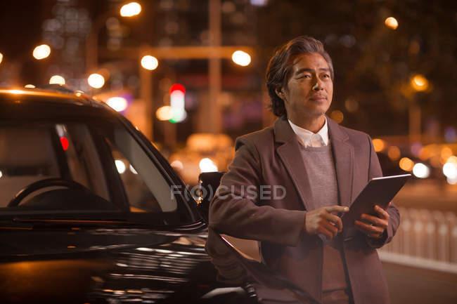 Maturo asiatico uomo in piedi vicino auto e utilizzando digitale tablet in notte città — Foto stock