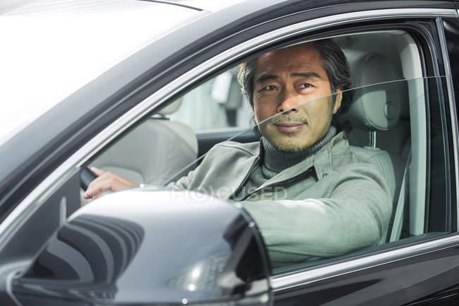Посміхаючись зрілий азіатських бізнесмен водіння автомобіля — стокове фото