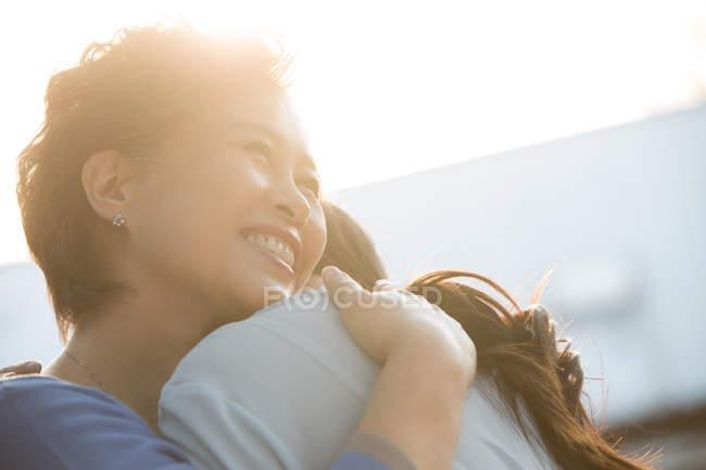 Счастливая пожилая мать обнимает молодую взрослую дочь — стоковое фото