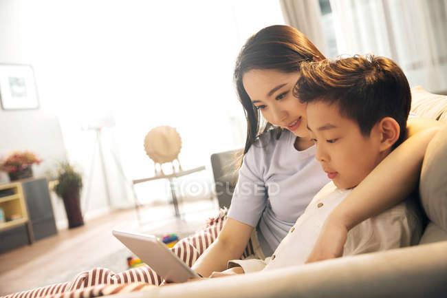 Felice madre asiatica con figlio utilizzando tablet digitale insieme a casa — Foto stock