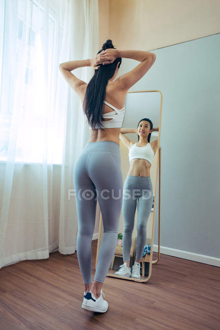 Back view of beautiful slim asian girl in sportswear looking at mirror — Stock Photo