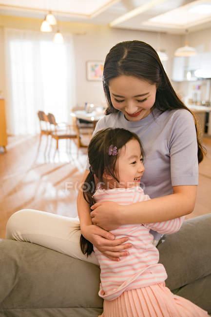 Красивая счастливая мать и дочь, обнимающиеся дома — стоковое фото