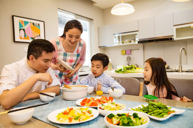 Happy asian family with two kids having dinner together at home — Stock Photo