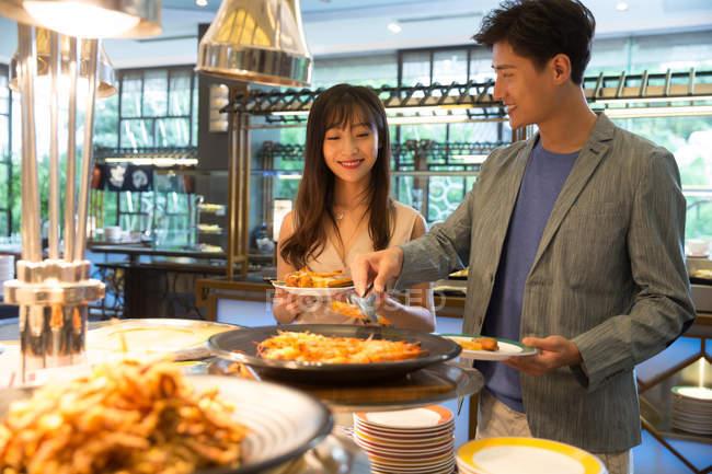 Glücklich junge asiatische Paar wahl leckeres Essen in Buffet — Stockfoto