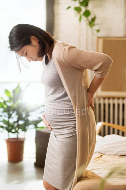 Вид сбоку молодой беременной женщины, прикасающейся к животу и спине — стоковое фото
