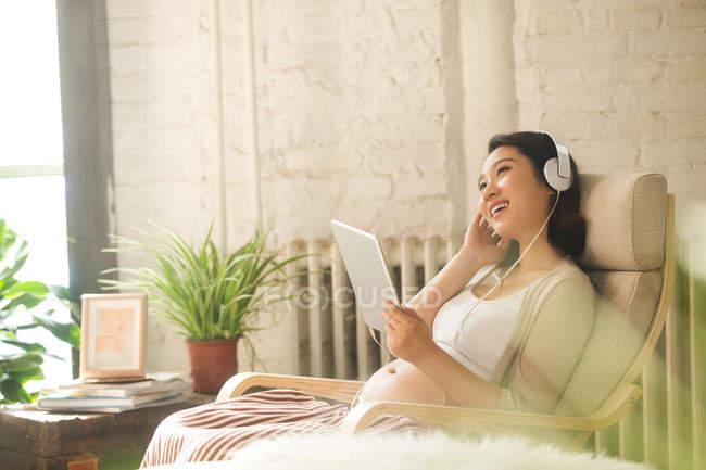 Souriant jeune femme enceinte dans les écouteurs en utilisant une tablette numérique à la maison — Photo de stock