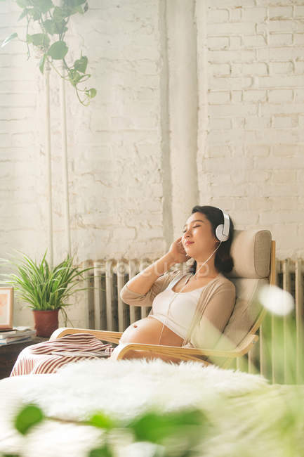 Smiling young pregnant woman with closed eyes sitting in rocking chair and listening music in headphones — Stock Photo