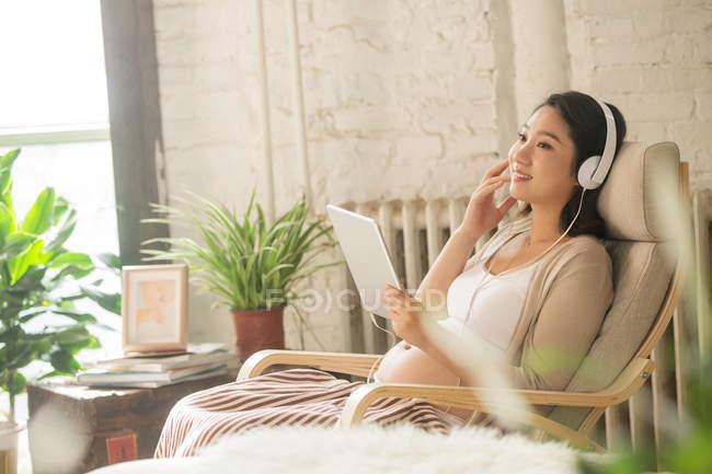 Sorrindo jovem grávida em fones de ouvido sentado em cadeira de balanço e usando tablet digital em casa — Fotografia de Stock