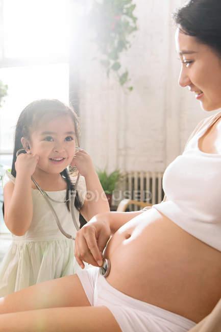Очаровательный улыбающийся ребенок, держащий стетоскоп и слушающий живот беременной матери — стоковое фото