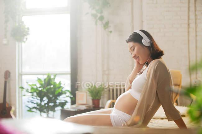 Вид сбоку улыбающейся молодой беременной женщины, слушающей музыку в наушниках дома — стоковое фото