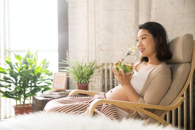 Вид сбоку улыбающейся молодой беременной женщины, сидящей в кресле и поедающей дома салат — стоковое фото