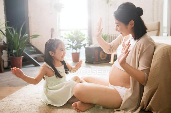 Вид сбоку на счастливого ребенка и беременную молодую мать, сидящую на полу и играющую вместе дома — стоковое фото