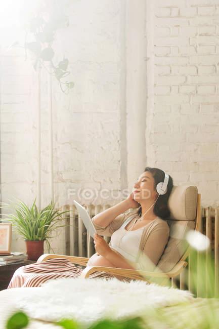 Молодая беременная китаянка в наушниках отдыхает в кресле и использует цифровой планшет дома — стоковое фото