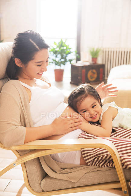 Adorable happy child hugging belly of pregnant mother at home — Stock Photo