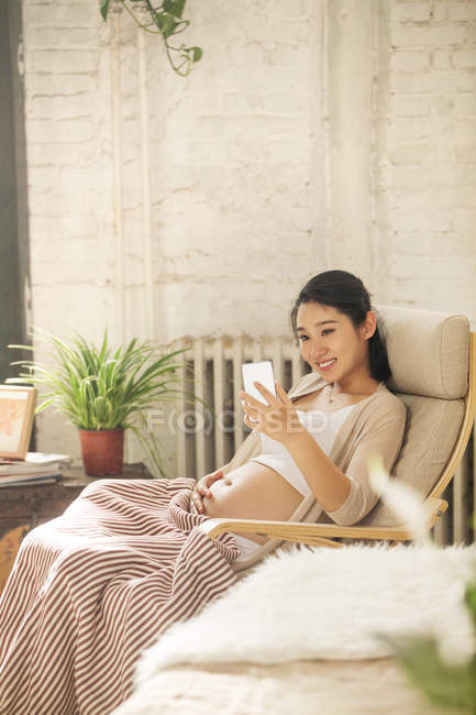 Smiling young pregnant woman sitting in rocking chair and using smartphone at home — Stock Photo