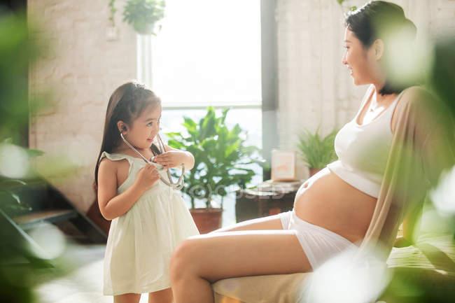 Селективное внимание очаровательного ребенка со стетоскопом, играющего с беременной матерью — стоковое фото