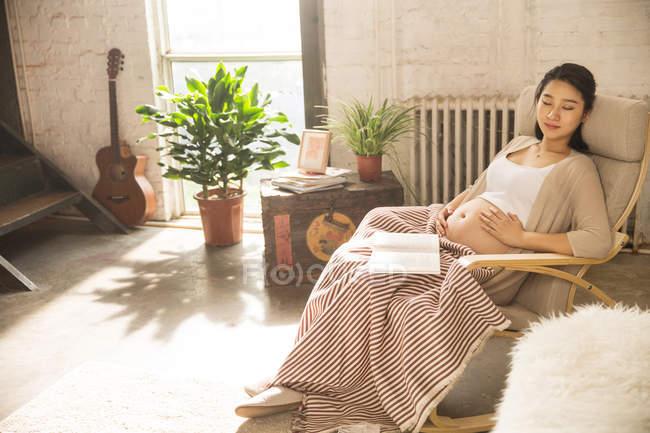 Счастливая молодая беременная женщина сидит в кресле-качалке с книгой — стоковое фото