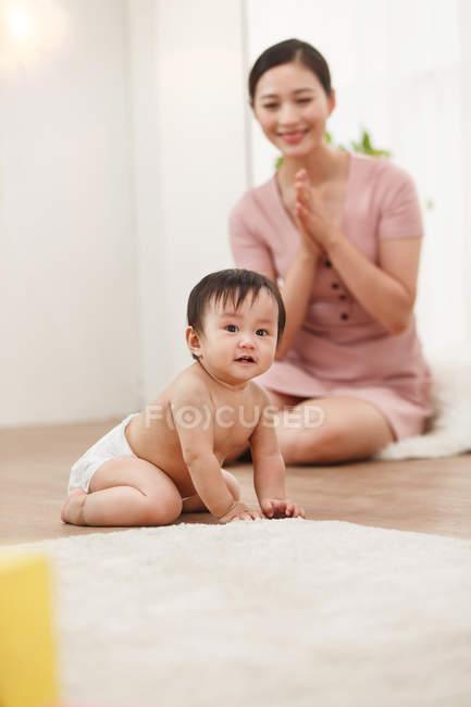 Счастливая молодая мать смотрит на восхитительного младенца-сумасшедшего на полу — стоковое фото