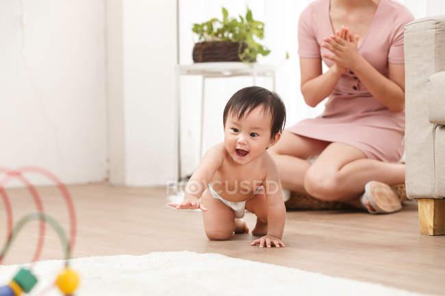 Чарівні щасливі дитини немовляти в пелюшки повзати на підлозі, а мати сидить позаду — стокове фото