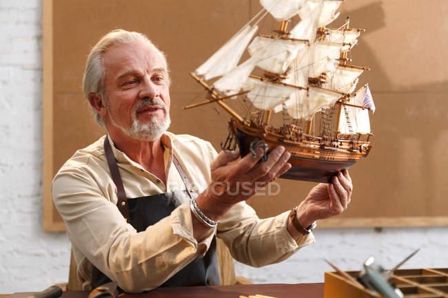 Smiling mature man making sailboat model at workshop — Stock Photo