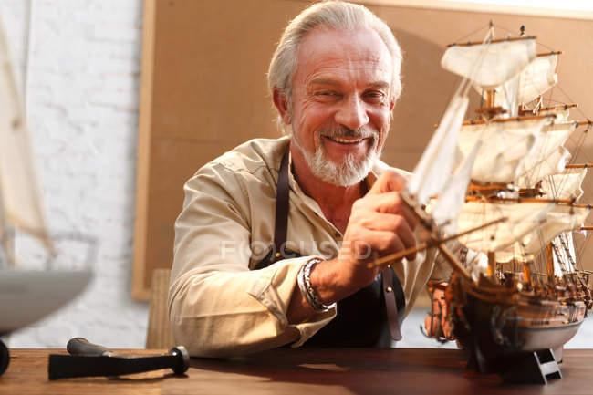 Lächelnder reifer Mann macht Segelboot Modell in der Werkstatt — Stockfoto